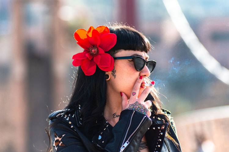 Alternative tattooed woman in leather jacket and sunglasses walking and smoking a cigarette