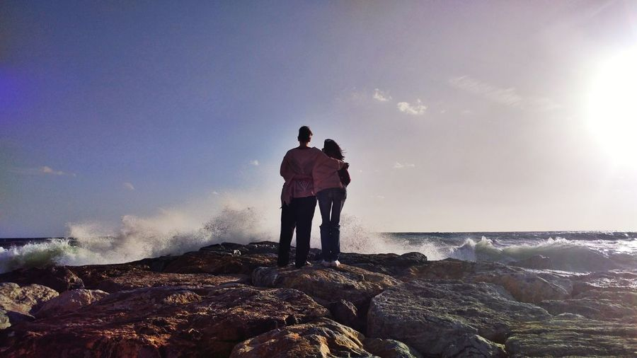 Rear view of friends standing at rocky shore against sky