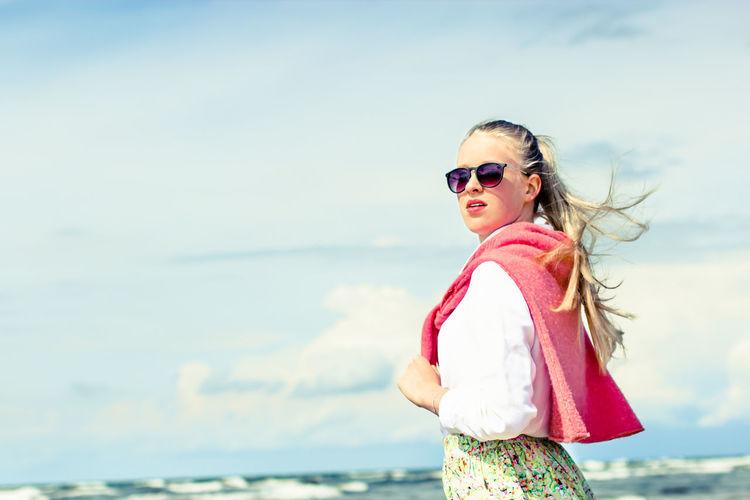 Portrait of woman wearing sunglasses at beach