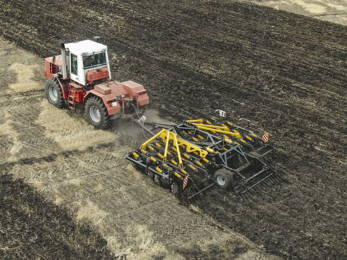 Aerial view of a modern tractor plowing dry field, preparing land for sowing Aerial Agriculture Field Tractor Farm Ground Soil Countryside Combine Machinery Motion Working Plowing Transportation Land Vehicle High Angle View Industry Environment Truck Landscape Construction Industry Mode Of Transportation Day Outdoors Equipment Nature