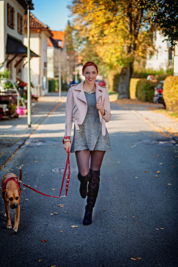 Portrait of woman with dog walking on road in city