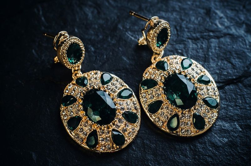 Gold earrings with green stones on a black background