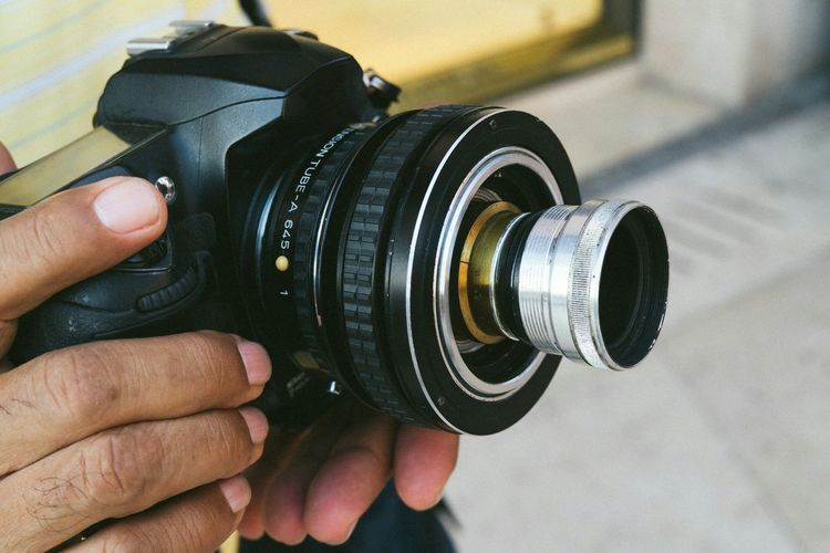 Cropped Shot Of Man Hand Holding Camera With Antique Lens