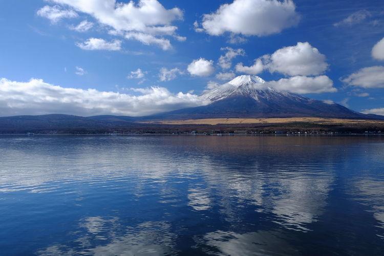 Mt Fuji By Lake Against Cloudy Sky