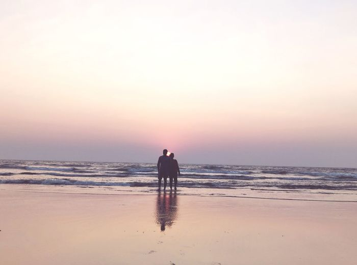 Couple on beach against sky during sunset