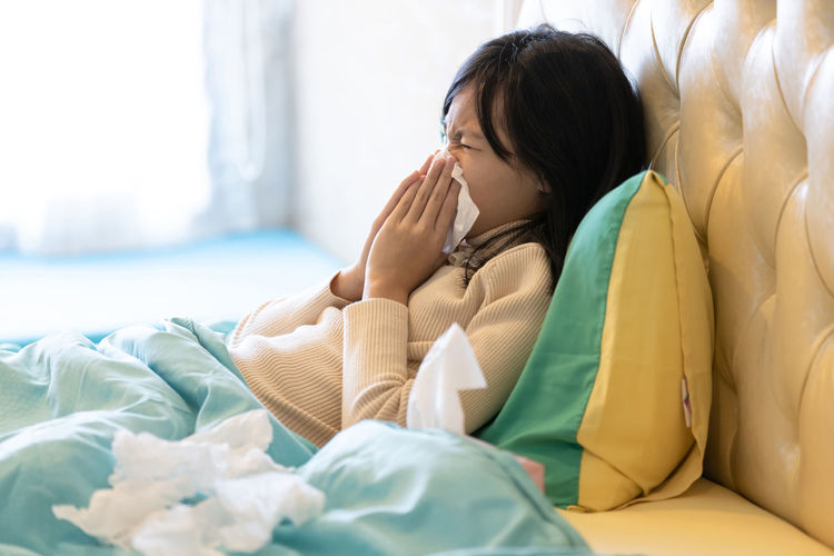 Side view of girl sneezing while lying on bed at home