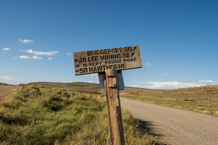 Hand carved letters on wooden road sign along rural dirt road against sky