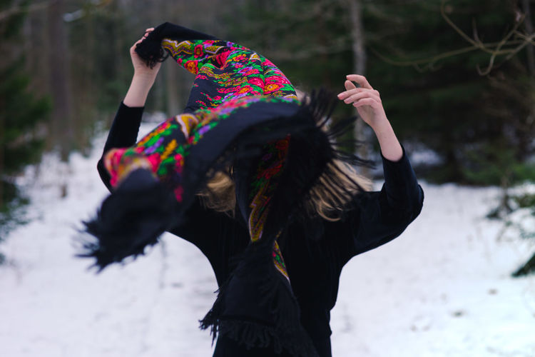 Woman Removing Scarf While Standing On Snow Covered Field