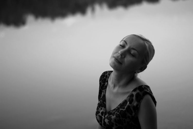 Young woman with eyes closed standing by lake