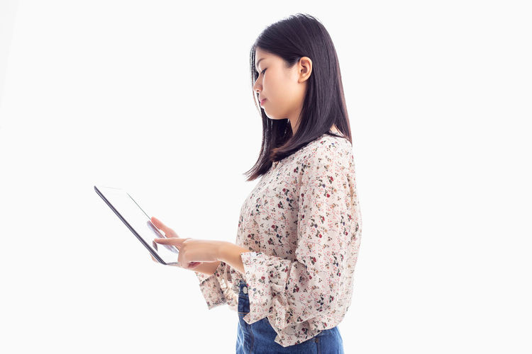Side view of young woman using smart phone against white background