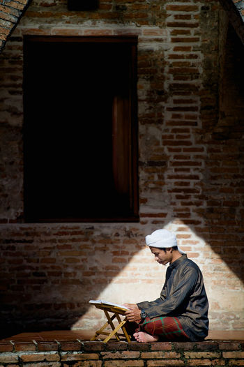 Side view of man reading book on table while sitting against brick wall