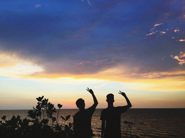 Silhouette people showing thumbs up sign by sea during sunset
