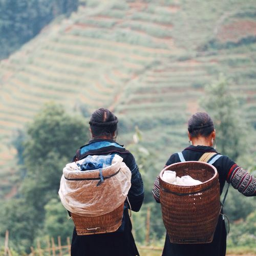 Rear View Of Women With Wicker Baskets On Field By Mountain