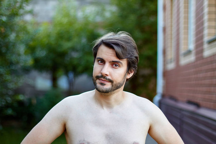 Portrait of shirtless man standing in yard