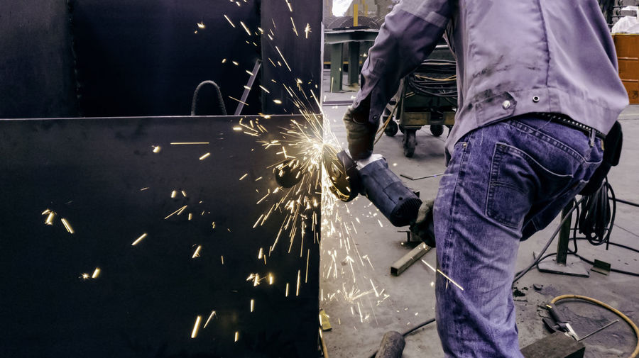 Midsection of man cutting metal