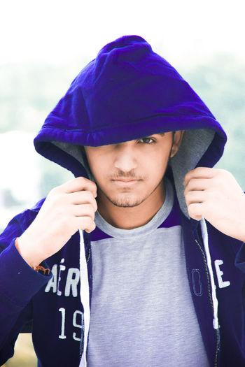 Close-up portrait of young man wearing hooded shirt