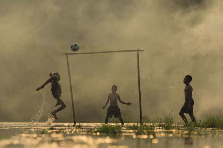 Shirtless Boys Playing Soccer On Wet Field During Monsoon
