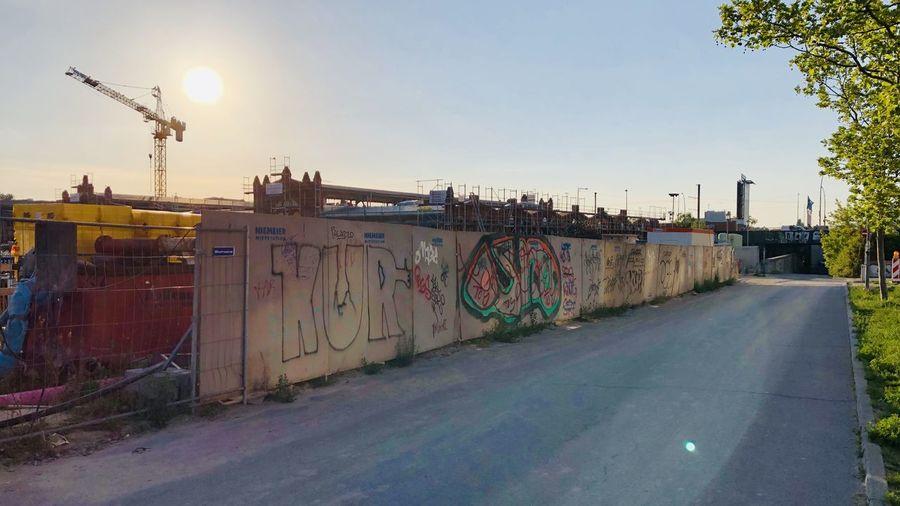 Graffiti on wall by street against sky