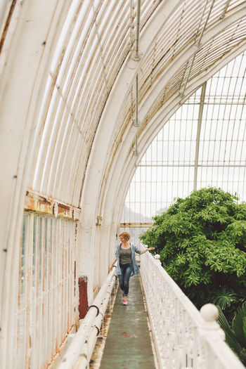 Full Length Of Woman Standing In Greenhouse