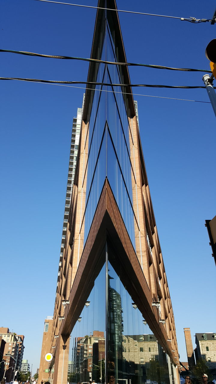 architecture, built structure, low angle view, building exterior, bridge - man made structure, clear sky, connection, outdoors, no people, day, blue, city, sky, tree