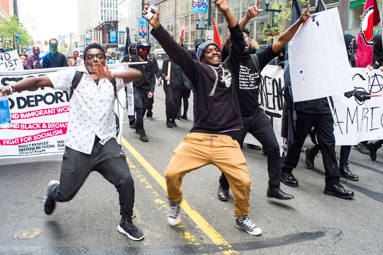 Three youth dance in front of the march during the International Workers Day March and Rally in Philadelphia, PA. Antifa Banner City Street Crowd Dancing Democracy Demonstration Immigrants March May Day 2017 Outdoors People Philadelphia Politics And Government Rally Signs Street