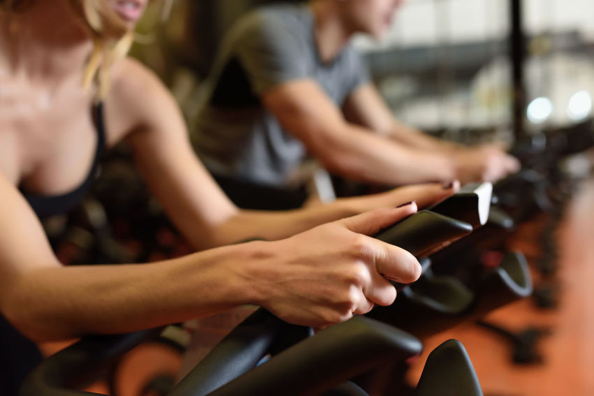Two people biking in the gym, exercising legs doing cardio workout cycling bikes. Couple in a spinning class wearing sportswear. Couple Man Woman Work Out Cardio Cardio Workout Cyclo Indoor Female Gym Healthy Healthy Lifestyle Indoors  Male Spinning Training Two People Young Adult