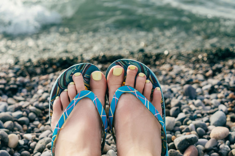 Low section of woman wearing flip-flop