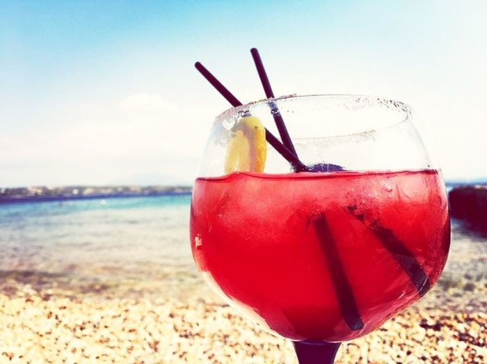 Close-up of red wine on beach against sky