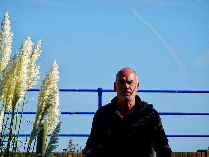 Portrait of man standing against blue sky