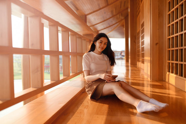 Portrait of young woman sitting on wooden floor