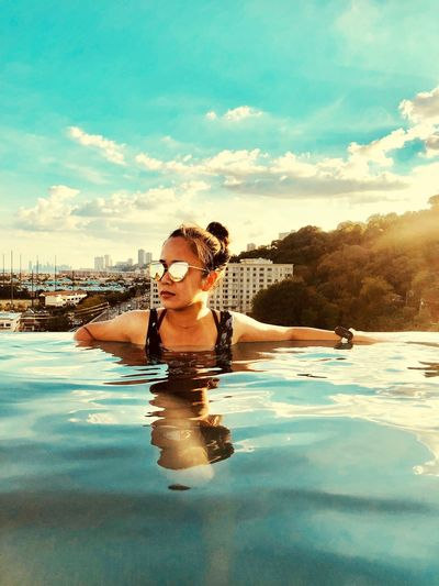 Young woman wearing sunglasses swimming in infinity pool against sky