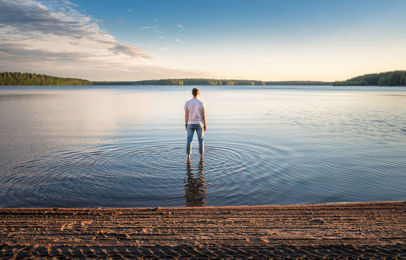 Man standing in water at beautiful summer day with idyllic lake and tranquil evening in Finland Water Rear View Full Length Lake One Person Sky Standing Scenics - Nature Nature Men Tranquility Beauty In Nature Adult Leisure Activity Tranquil Scene Reflection Outdoors Looking At View Day Standing Landscape Evening Light Finland Warm Travel Destinations