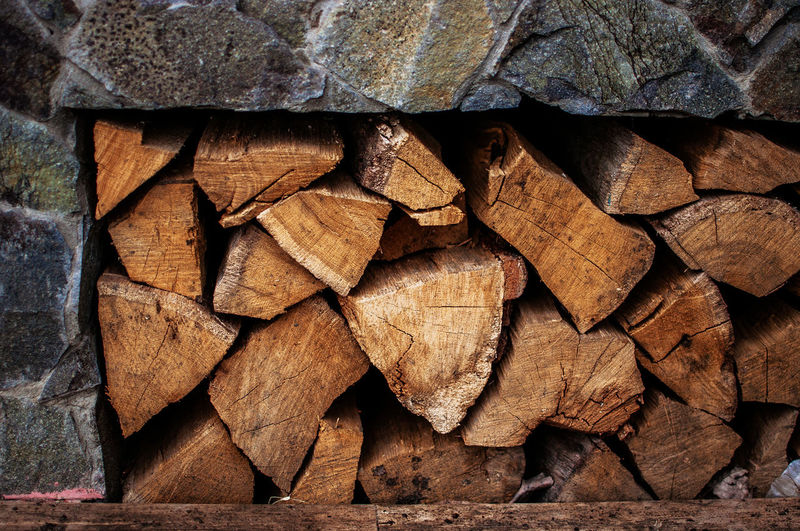 chopped firewood for the fireplace lies in a stone cell for materials for fire.