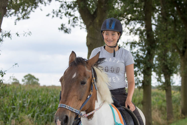 Happy teenager riding horse