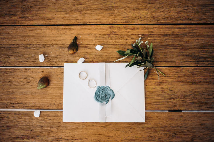 Wedding rings on the wooden table with letter and figs