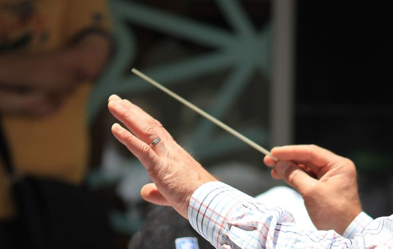 Cropped image of musical conductor holding stick