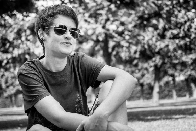 Portrait of young man wearing sunglasses sitting at park