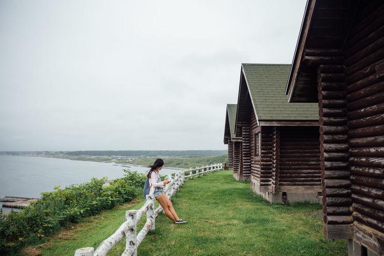 Full Length Of Woman Standing On Shore Against Sky
