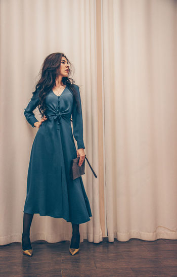 Full length of woman standing against curtain