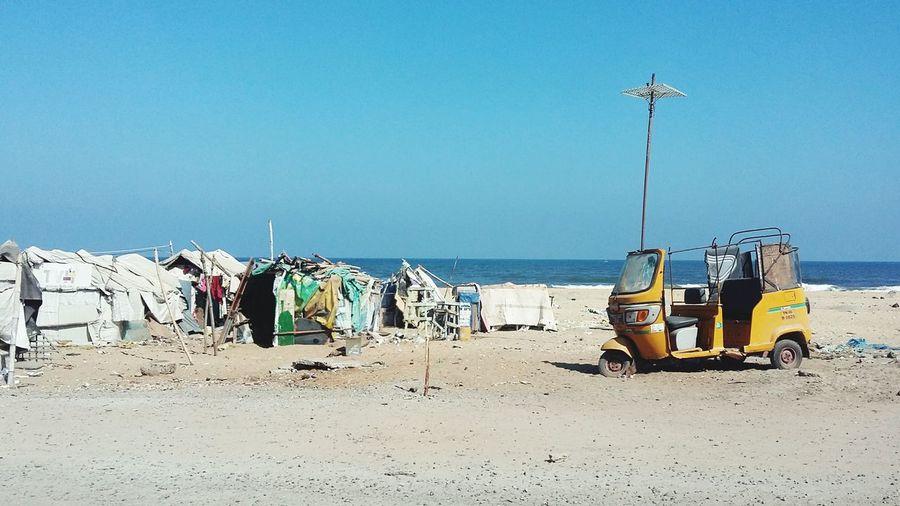 Abandoned rickshaw at beach against clear blue sky