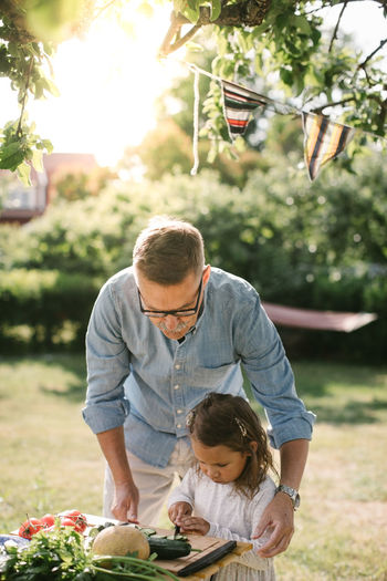 Full length of father with daughter against plants