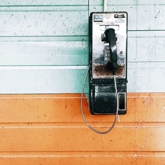 Close-up of old pay phone mounted on wall