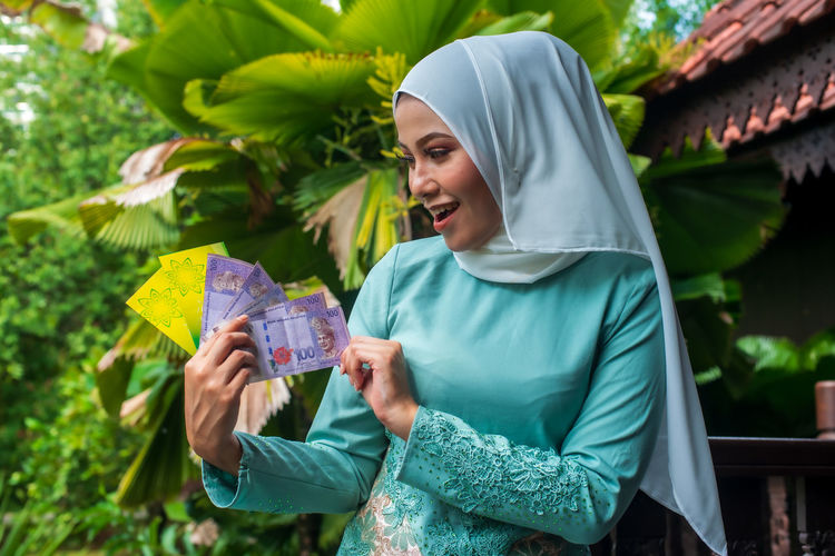 Smiling young muslim woman holding money and envelope while sitting outdoors during eid