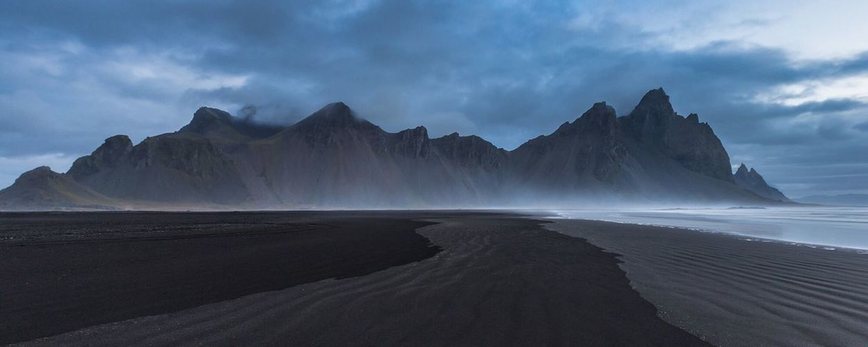 Panoramic View Of Mountains At Beach Against Cloudy Sky