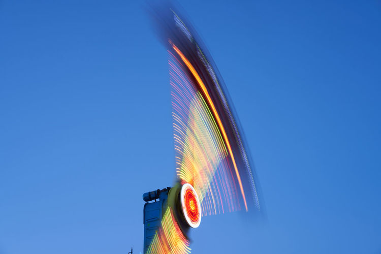 Low angle view of illuminated spinning propeller against sky