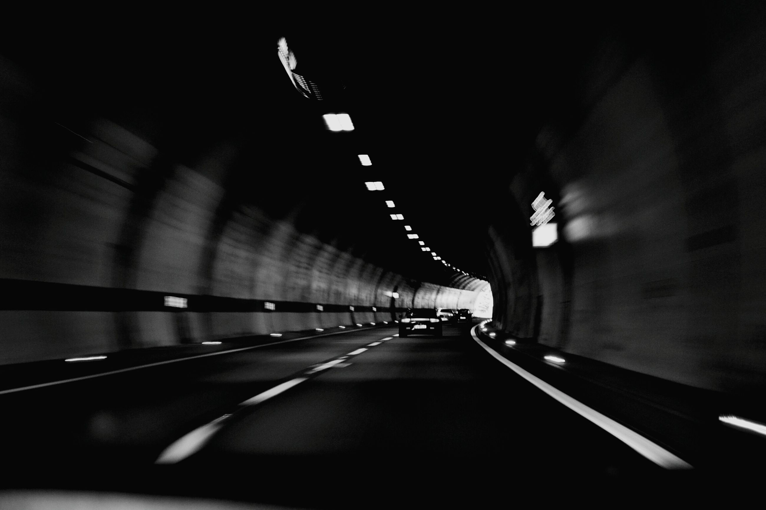 transportation, the way forward, illuminated, diminishing perspective, tunnel, vanishing point, road marking, road, indoors, mode of transport, night, on the move, blurred motion, travel, motion, empty, lighting equipment, land vehicle, underground, long