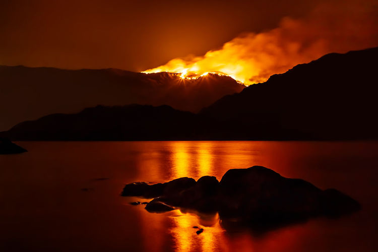 Forest fire at night reflecting in nearby lake. Creek Flame Hot Natural Nature Orange Red Silhouette Smoke Trees Burn Danger Disaster Environmental Conservation Environmental Damage Environmental Protection Fire Forest Forest Fire Lake Mountains Night Sky Wild Wildfire