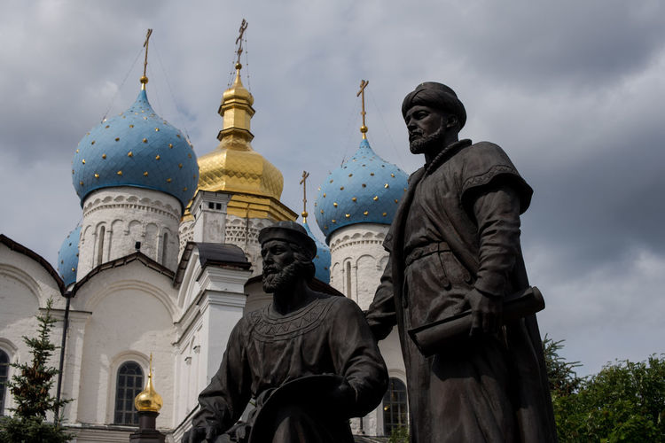 Statues and russian orthodox church against cloudy sky