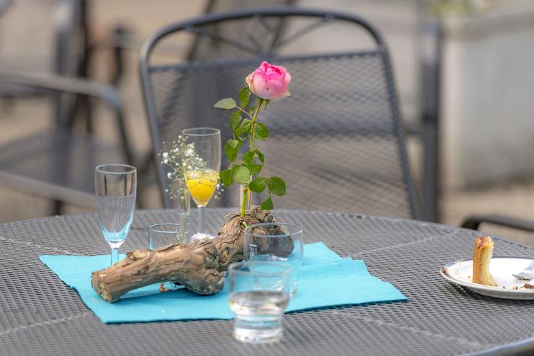 Flower vase on table against glass wall