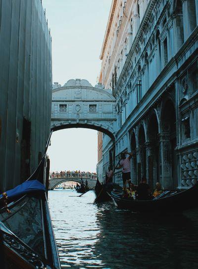 People in gondola amidst buildings